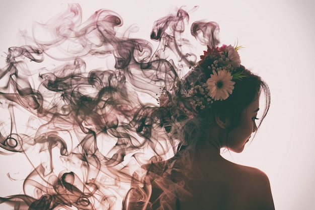 Fille asiatique est belle et charmante avec la couronne de fleurs. elle s'évapore en fumée de parfum. flare style de lumière. Photo Premium
