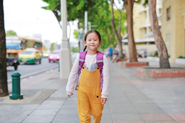 Fille asiatique heureuse enfant marchant avec cartable épaule d'étudiant. Photo Premium