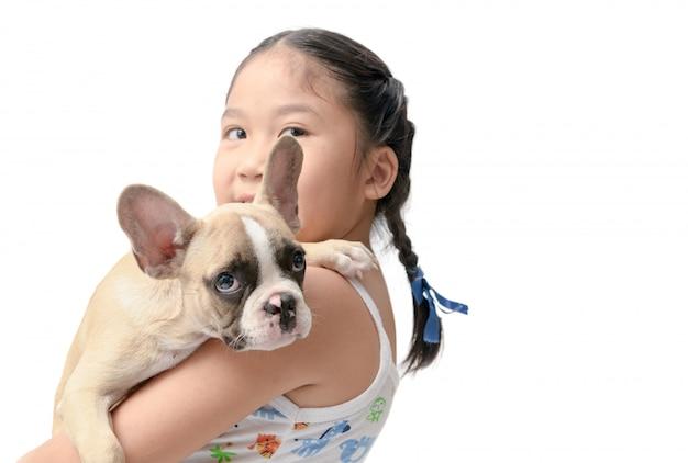 Fille asiatique heureux enfant tenant le bouledogue français Photo Premium