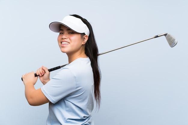 Fille asiatique jeune golfeur sur mur bleu isolé Photo Premium