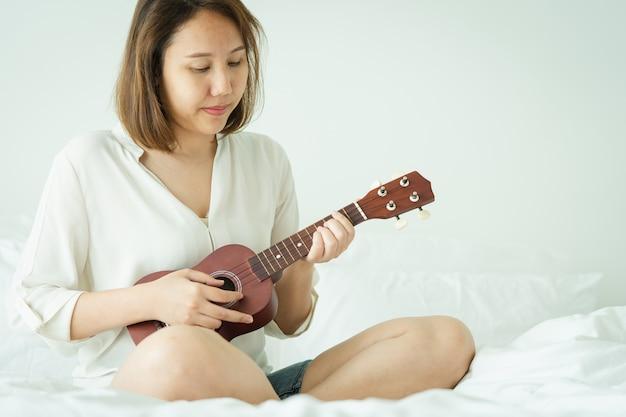 Fille asiatique jouer l'ukelele Photo Premium