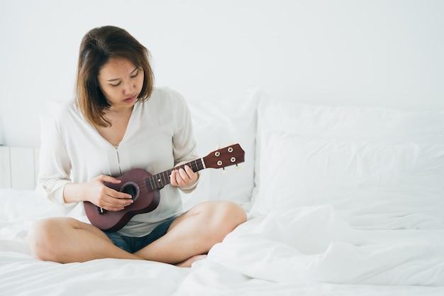 Fille asiatique jouez de la guitare dès le lever du matin. le rendre brillant Photo Premium