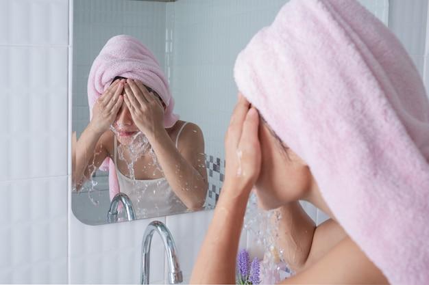 Fille asiatique lave le visage. Photo gratuit
