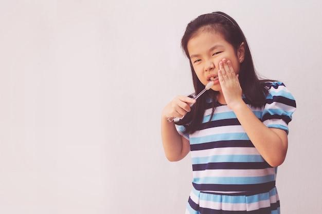 Fille Asiatique A Un Mal De Dents Tenant Une Brosse à Dents Photo Premium