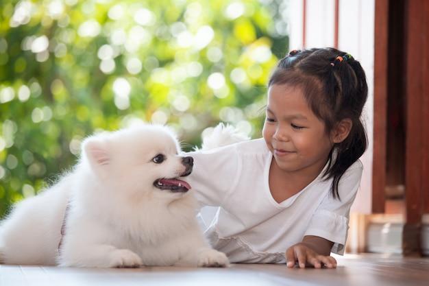 Fille asiatique mignonne jouant avec son chien spitz avec plaisir et bonheur Photo Premium