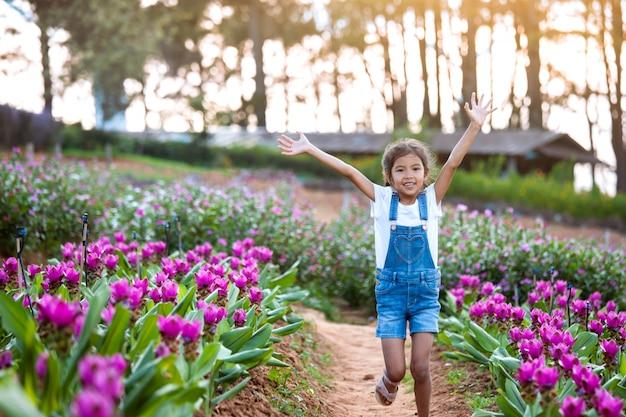 Fille asiatique mignonne lève les bras et courir dans le jardin fleuri Photo Premium