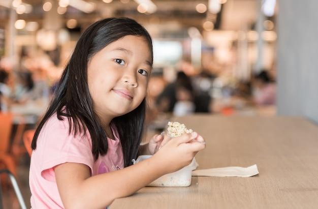 Fille asiatique mignonne manger boîte déjeuner dans l'aire de restauration, concept de fastfood Photo Premium