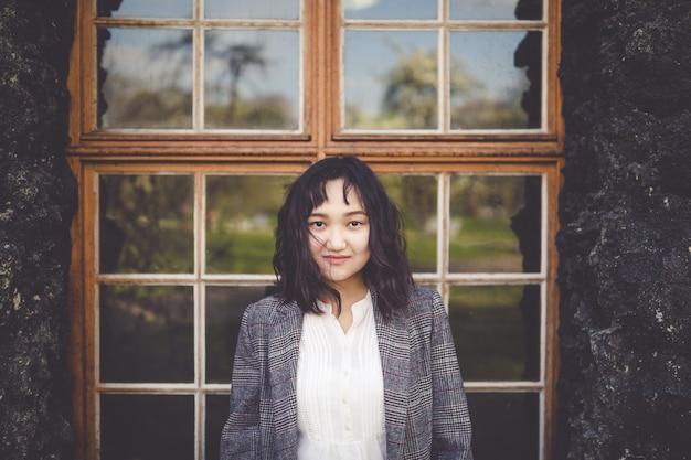 Fille asiatique optimiste devant le bâtiment rustique Photo Premium