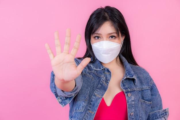 Une Fille Asiatique Portant Un Masque Facial Montre Le Geste Des Mains D'arrêt Pour Arrêter L'épidémie De Virus Corona, Protéger La Propagation De Covid-19 Photo gratuit
