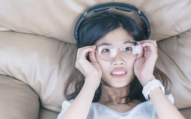 Fille asiatique ringard avec des lunettes écoute de la musique sur son casque Photo Premium
