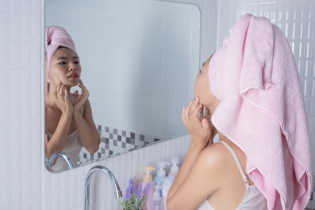 Fille asiatique serre l'acné. Photo gratuit