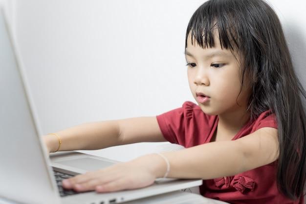Fille asiatique travaillant sérieusement sur un ordinateur portable. s'exercer à utiliser des appareils technologiques. Photo Premium