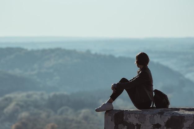 Fille Assise Sur La Colline Et Regarde Au Loin Dans La Forêt. Brume Photo Premium