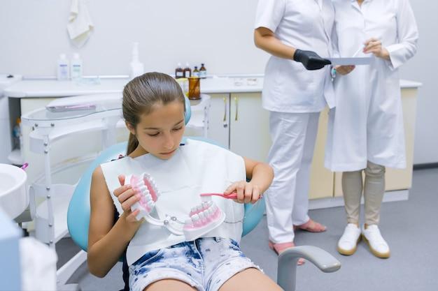 Fille Assise Dans Le Bureau Du Dentiste étudiant Le Modèle De La Mâchoire Dentaire Photo Premium