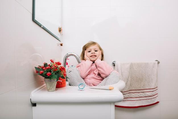 Fille assise dans le lavabo de la salle de bain avec des pots de fleurs Photo gratuit
