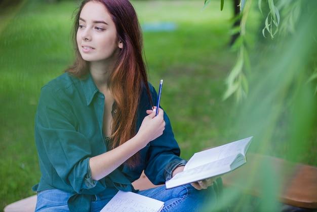 Fille Assise Dans Un Livre De Parc Photo gratuit