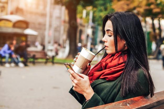 Fille Assise Dans Le Parc Avec Café Et Téléphone Photo Premium