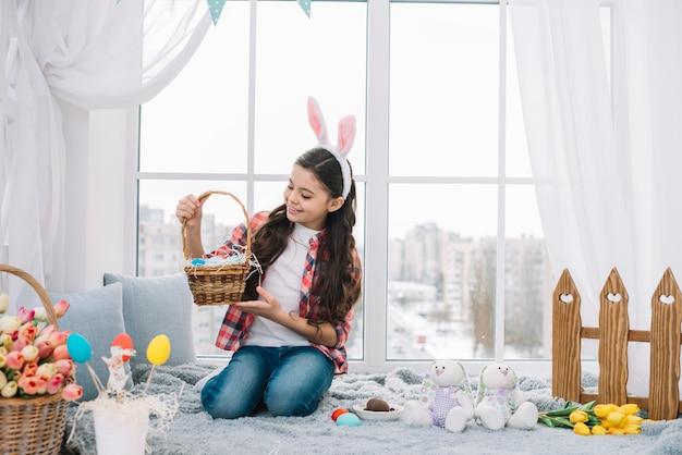 Fille assise sur le lit en regardant le panier d'oeufs de pâques à la maison Photo gratuit