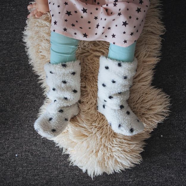 Fille assise sur la peau d'agneau sur le sol Photo Premium