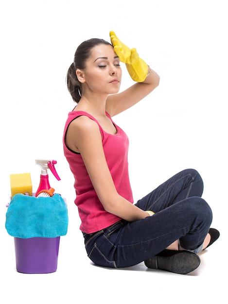 Fille assise avec des produits de nettoyage et au repos. Photo Premium