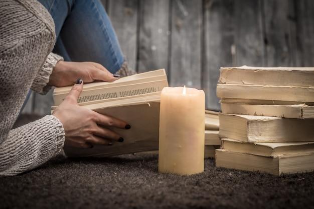Fille Assise Sur Le Sol Entouré De Nombreux Livres Blancs Et Une Grande Bougie Photo gratuit