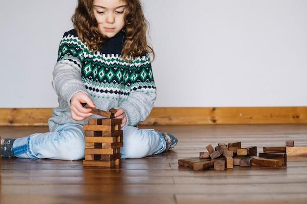 Fille assise sur le sol en jouant au jeu jenga Photo gratuit