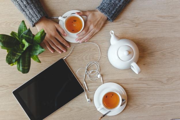 Fille assise à la table et boit du thé vert. vue de dessus Photo Premium