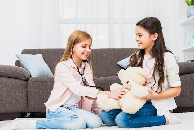 Fille assise sur un tapis jouant avec peluche à l'aide d'un stéthoscope dans le salon Photo gratuit