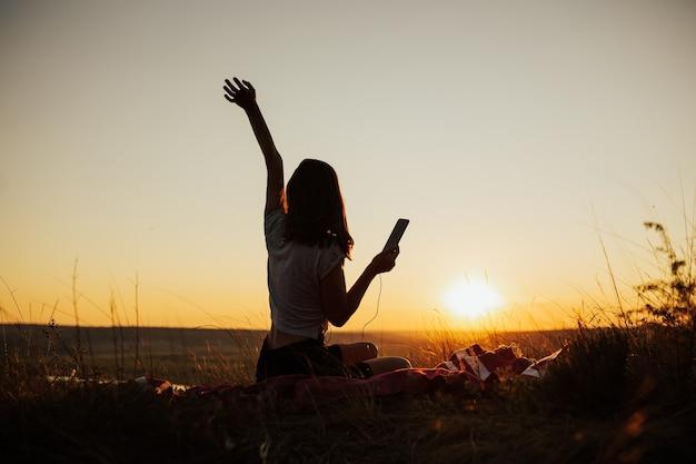 Fille Assise Sur Le Terrain Au Coucher Du Soleil Magnifique Et Profiter De L'écoute De La Musique à L'aide De L'application De Téléphone Mobile Avec Des écouteurs Au Coucher Du Soleil. Photo Premium