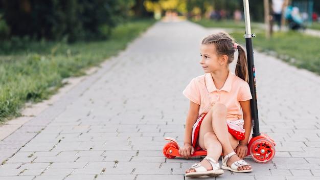 Fille assise sur un trottinette sur la passerelle droite Photo gratuit