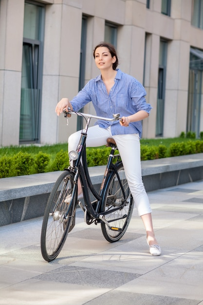 Fille Assise Sur Un Vélo Dans La Rue Photo gratuit