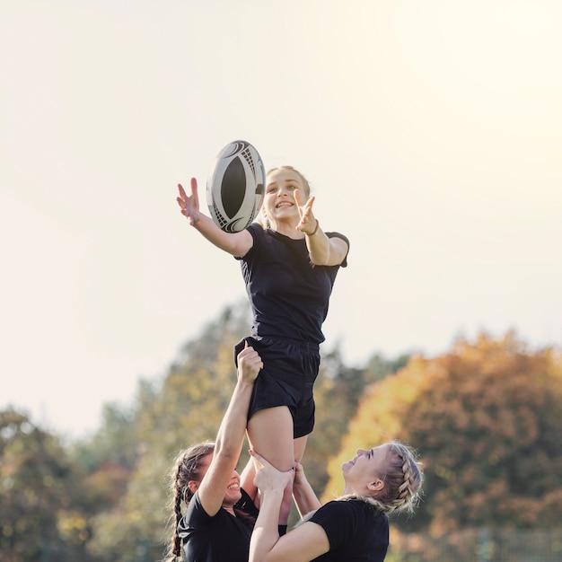 Fille Attraper Un Ballon Aidé Par Ses Coéquipiers Photo gratuit