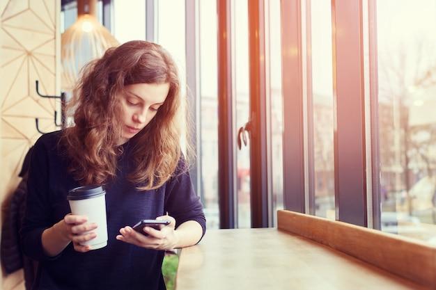 La fille au café boit du café et utilise le téléphone Photo Premium