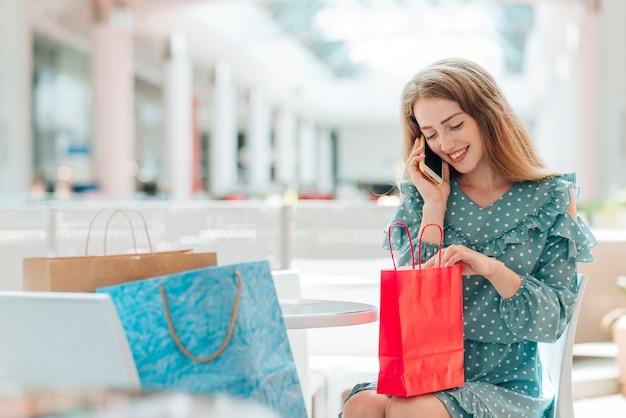 Fille au centre commercial parlant au téléphone Photo gratuit