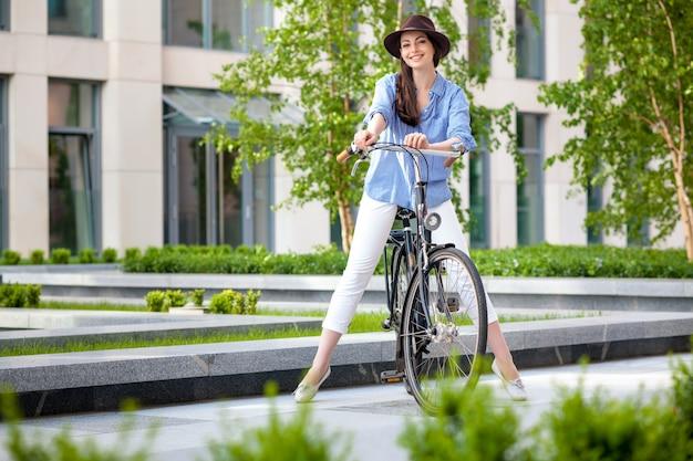 Fille Au Chapeau, Faire Du Vélo Dans La Rue Photo gratuit