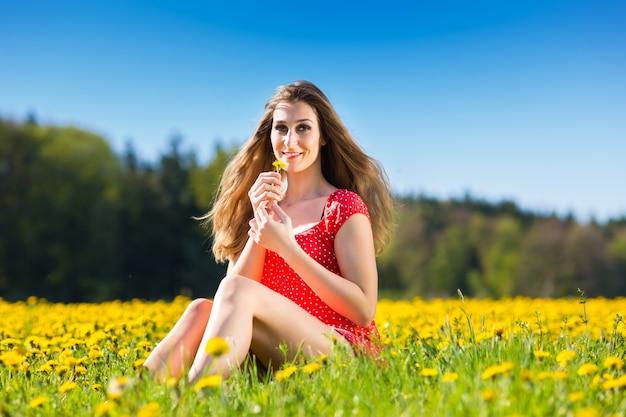 Fille au printemps sur un pré de fleurs avec pissenlit Photo Premium