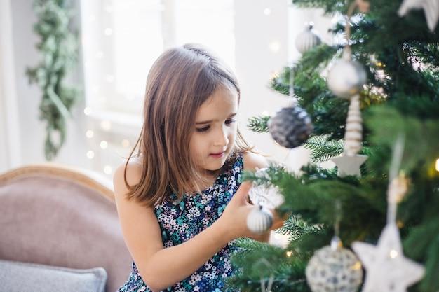Fille autour du sapin de noël, en attente de cadeaux et de vacances, traditions de noël, noël et famille Photo Premium