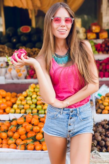 Fille Aux Cheveux Longs Et Bon Corps Sur Le Marché Des Fruits Tropicaux. Elle Porte Des Lunettes De Soleil Roses, Tient Des Fruits De La Passion Et Sourit Photo gratuit