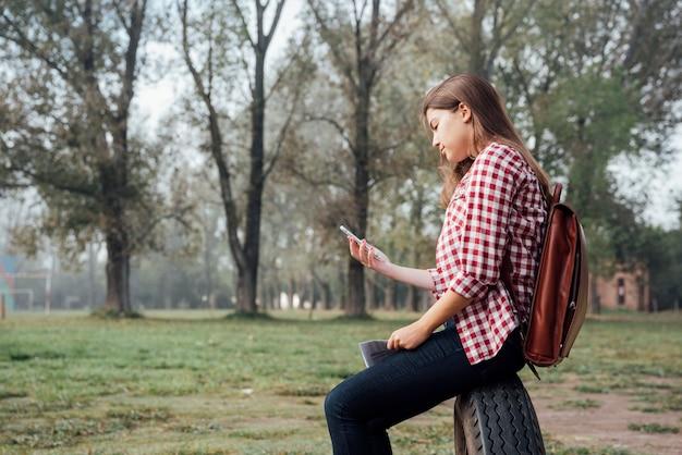 Fille aux cheveux longs vérifiant son téléphone Photo gratuit