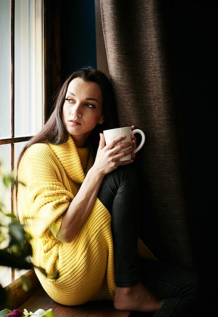 Fille aux cheveux noirs imaginée regarde par la fenêtre et boit du thé Photo gratuit