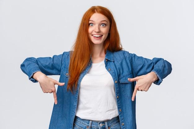 Fille Aux Cheveux Rouges Souriant Fasciné Pointant Les Doigts Vers Le Bas Photo Premium
