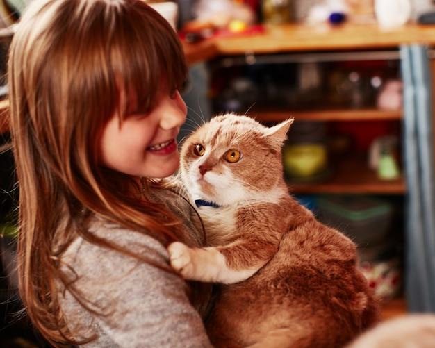La fille aux cheveux roux tient le chat aux cheveux roux Photo gratuit