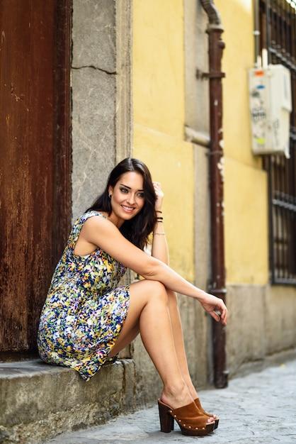 Fille aux yeux bleus souriant assis sur une marche urbaine. Photo Premium