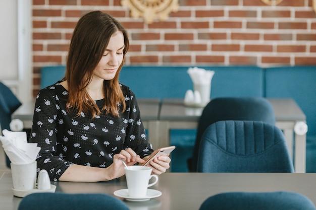 Fille ayant un café au restaurant Photo gratuit