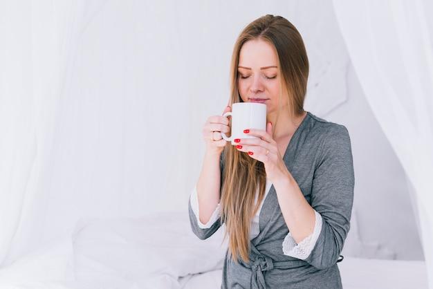 Fille ayant du café au lit Photo gratuit