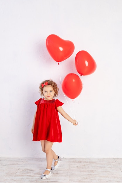 Fille Avec Des Ballons En Forme De Coeur Dans Une Robe Rouge Sur Fond Blanc, Le Concept De L'amour Et De La Saint-valentin Photo Premium