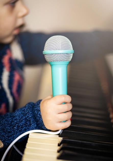 Fille en bas âge, piano et micro jouet. Photo Premium