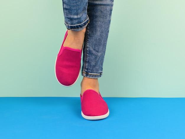 Fille En Baskets Rouges Et Jeans Déchirés Marchant Sur Le Sol Bleu. Photo Premium