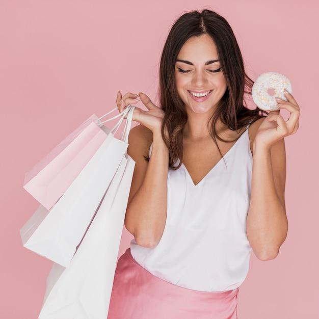 Fille avec un beignet et sacs à provisions sur fond rose Photo gratuit