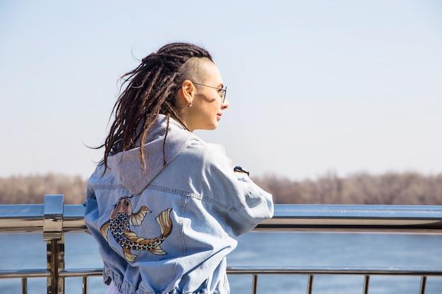 Fille belle à la mode moderne seule sur une promenade de printemps au bord de la rivière Photo Premium